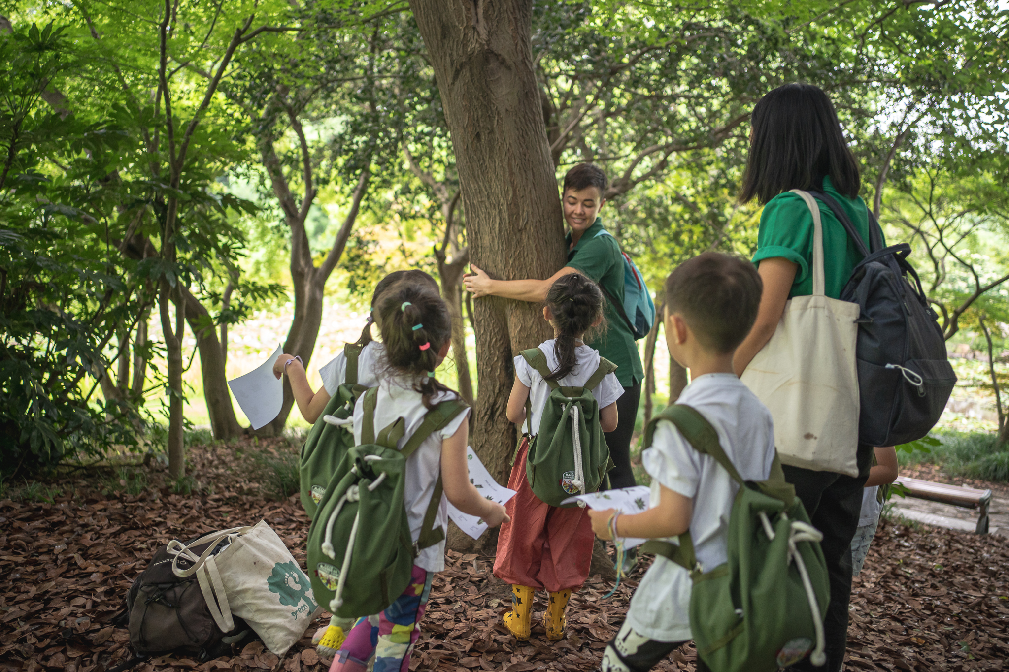 young nature guide hugs tree wit class of children
